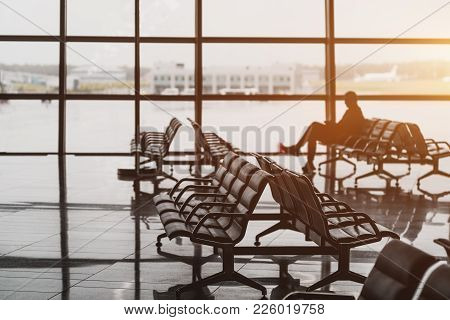Waiting Room In Airport Terminal Departure Area Near Gates: Hall With Rows Of Armchairs, Glass Facad