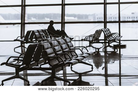 Silhouette Of Man Sitting On Armchair Next To Glass Window Of Modern Waiting Hall In Departure Area