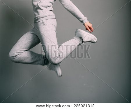 Girl In Gray Suit And White Sneakers Jumps High With Her Legs Up