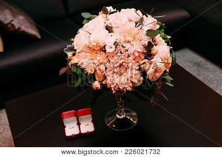 Rings Cartier In A Red Box On A Table With A Bouquet Of Flowers On Stend