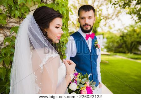 Focus Of Beautiful Married Woman With Pink Bouquet And Man Behind With Velvet Tie-bow And A Beard