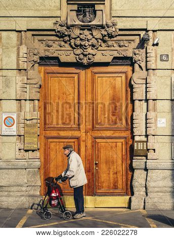 Milan, Italy - Feb 10, 2018: Older Man In Front Of Gothic Facade And Huge Wooden Door In Milan, Lomb