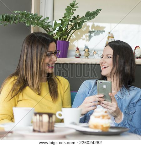 Two Beautiful Girls Enjoy Coffee And Cakes And Use A Mobile Phone