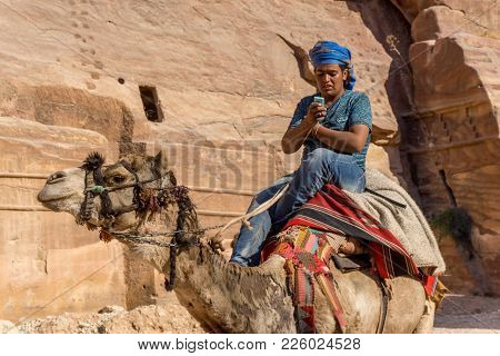 April 2017: Bedouin Riding A Camel While Texting At Petra, Jordan Shows The Clash Of Traditional And
