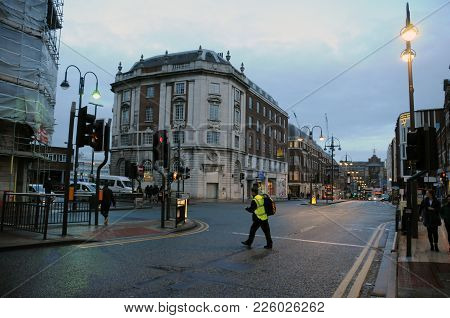 Leeds, England - January 08, 2018: Man In A High Visibility Jacket Crossing The Road On The Headrow