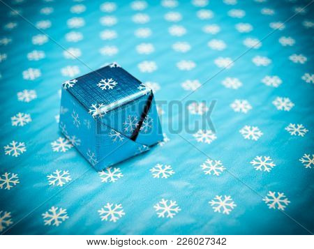 Just One Wrapped Chocolate Candy On A Blue Background.