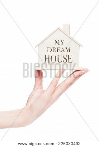 Female Hand Holding Wooden House Model With Conceptual Text. My Dream House