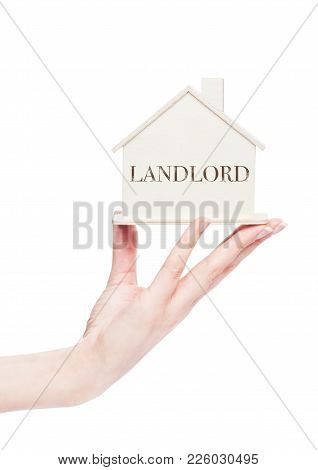 Female Hand Holding Wooden House Model With Conceptual Text. Landlord