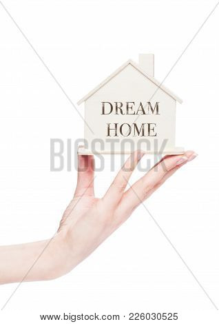 Female Hand Holding Wooden House Model With Conceptual Text. Dram Home