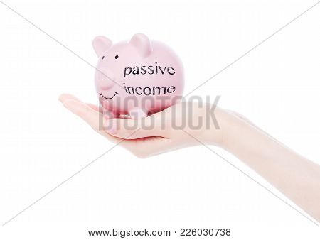 Female Hand Holds Piggy Bank With Passive Income Concept Text