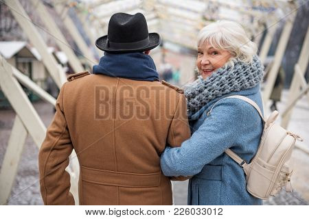 Portrait Of Happy Old Woman Looking Back With Interest While Walking Arm In Arm With Man. She Is Lau