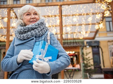 Waist Up Portrait Of Joyful Mature Woman Waiting With Present Outdoor. Copy Space