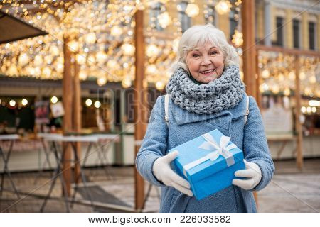 Waist Up Portrait Of Happy Senior Woman Giving Present With Generosity. She Is Standing Outdoor And