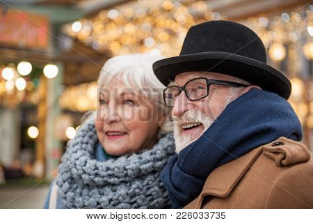 Focus On Happy Old Man Looking Forward And Smiling While Walking With Woman In Town
