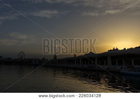 Giantwheel And The Docking Harbour Of Malaga With Sun Set In The Background In Malaga, Spain, Europe