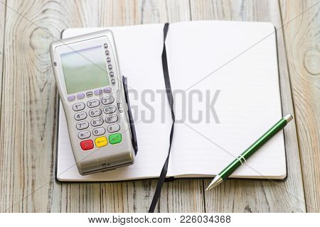 Modern Technology And People Concept - Pos Terminal And Notepad. Rough Bords Background. Closeup