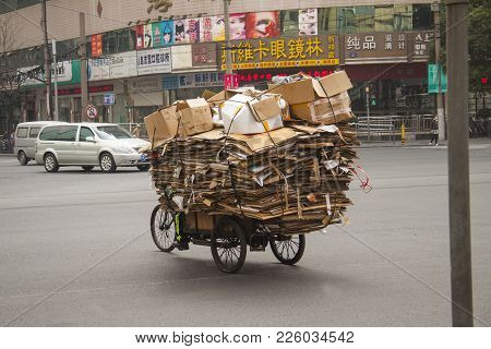 Shanghai, China, December 31, 2014: Man Rides Overloaded  Bicycle With Folded  Cardboard Boxes