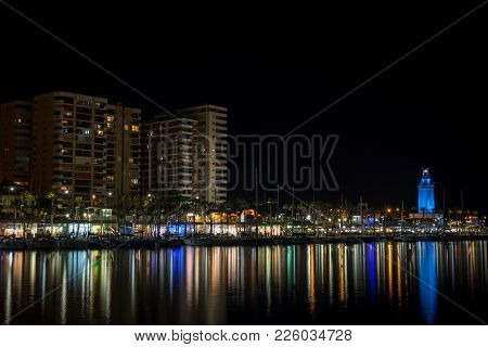 View Of Malaga City And Lighthouse And Their Reflections On Water From Harbour, Malaga, Spain, Europ
