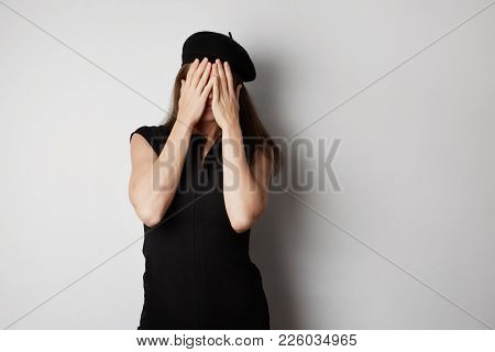 Woman Afraid Of Look Through Your Fingers. On A White Background.