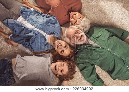 Top View Portrait Of Cheerful Bearded Grandfather, Outgoing Grandma, Beaming Lady And Glad Son Lying