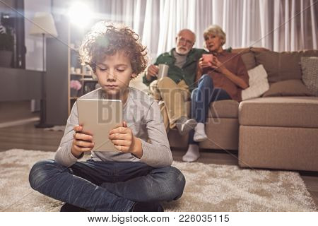 Full Length Portrait Of Serene Child Typing In Electronic Tablet While Locating On Carpet In Room. C