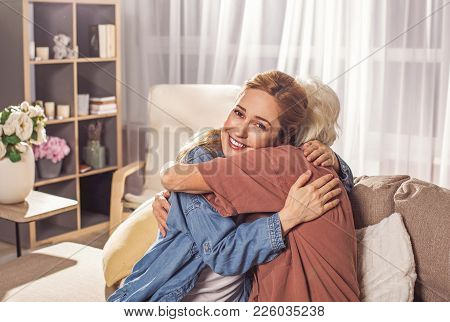 Outgoing Lady Hugging Granny In Room. She Turning Back To Camera. Family Concept