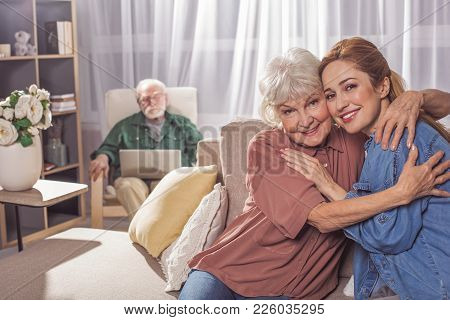 Portrait Of Glad Grandmother Hugging Smiling Woman. They Looking At Camera While Sitting On Sofa. Fa