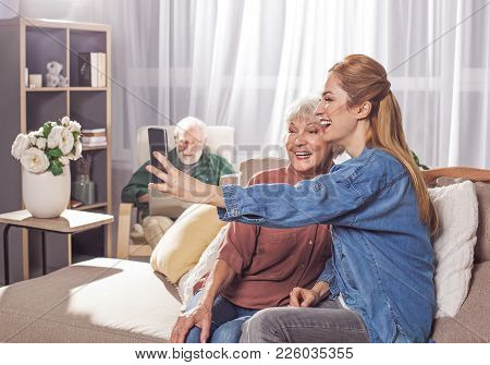 Outgoing Grandma And Cheerful Woman Taking Selfie By Phone While Sitting On Sofa. Granddad Looking A