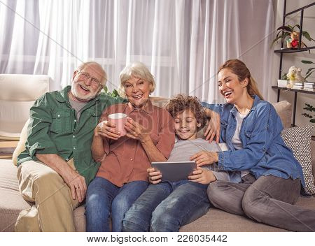 Portrait Of Happy Grandpa, Smiling Child, Glad Grandmother And Laughing Mom Resting On Couch. Son Lo