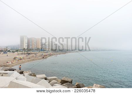 The Building Along The Coastline At Malagueta Beach Covered By Fog In Malaga, Spain, Europe