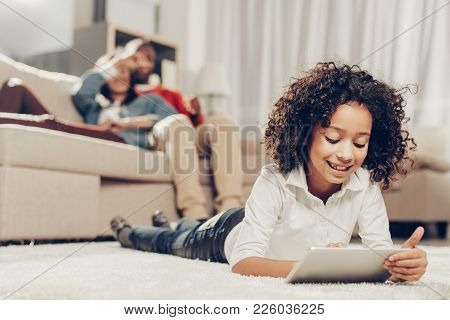 Portrait Of Smiling Girl Lying On Carpet Indoors And Using Tab. Focus On Child. Mom And Dad Are Rest