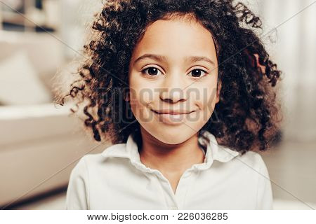 Portrait Of Cheerful African Child With Curly Hair Looking At Camera With Delight. Focus On Girl