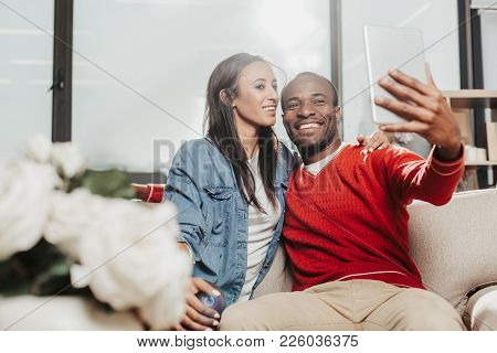 Smile. Content Espoused Man And Woman Sitting On Cozy Sofa And Taking Photo Of Themselves. Copy Spac