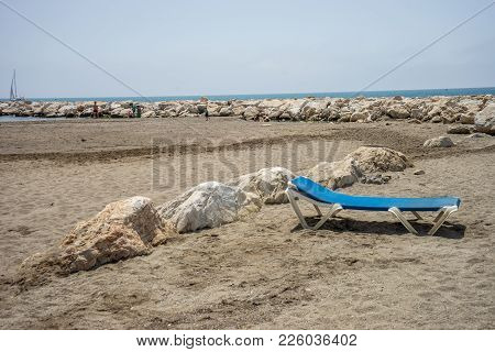Sunbed On The Rocky Beack At Malagueta In Malaga, Spain, Europe On A Cloudy Morning With The Ocean A