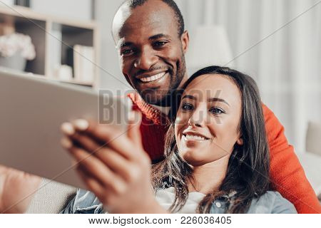 Portrait Of Two Amorous Person Spending Time With Device At Home. Their Faces Expressing Enjoyment