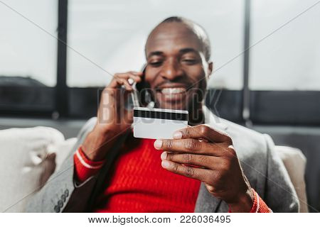 Portrait Of Smiling Guy Sitting On Couch And Communicating By Cellphone. Focus On Bankcard In His Ar