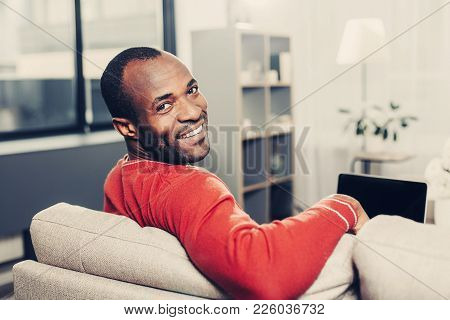 Portrait Of Cheerful Man Sitting On Sofa With Laptop At Home. He Is Looking At Camera And Smiling