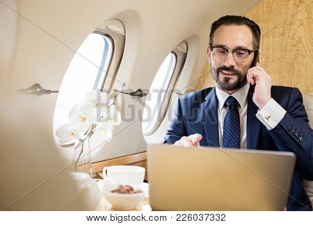 Portrait Of Glad Diplomat In Airplane Talking By Cellphone And Looking At Notebook Screen. Copy Spac