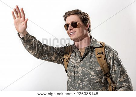 Joyful Young Male Officer Waving His Hand To Somebody And Having Knapsack On His Shoulders. He Is Sm