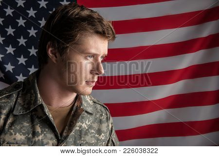 Sedate Young Soldier Standing On Background Of The Flag With Serious Look. His Head Is Turned Aside.