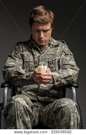 Portrait Of Cheerless Handicapped Male Veteran Holding Candle And Looking At It. He Is Sitting In In