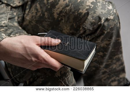 Close Up Of Male Hand Holding The Bible. Disabled Male Veteran Sitting And Praying. He Is Wearing Mi