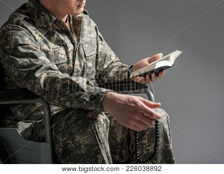 Disabled Veteran Sitting In Invalid Chair. He Is Holding Rosary And The Book In His Hands. Isolated