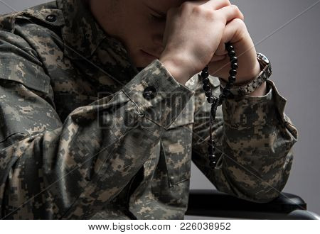 Paralyzed Military Young Man Sitting In Wheelchair. He Is Holding Beads In His Hands And Praying Wit