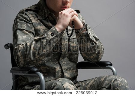 Disabled Soldier Holding Rosary In His Hands. He Is Sitting In Invalid Chair And Wearing Military Un