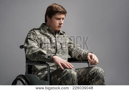 Upset Disabled Soldier Feeling Helpless. He Is Looking Down And Sitting In Invalid Chair With Sad Lo