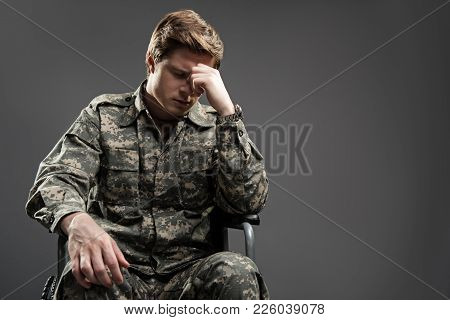 Despondent Handicapped Soldier Sitting In Wheelchair With Closed Eyes. He Is Feeling Hopeless For Hi
