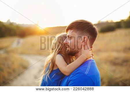Family Values. Father Hugs And Holds A Small Daughter In His Arms. They Are Walking In The Field At