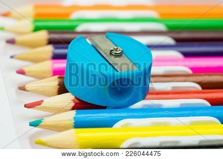 Pencil Sharpener On Colorful Pencils Background. School Stationery