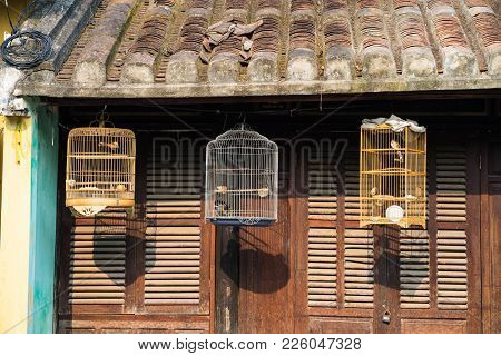 Three Birdcages In Front Of Old House